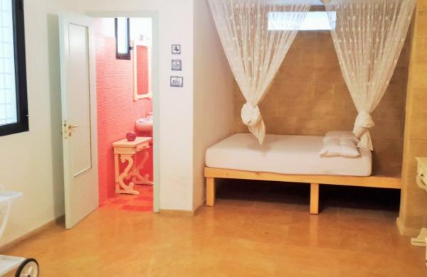 Locale attiguo con letto matrimoniale e bagno con lavabo e WC